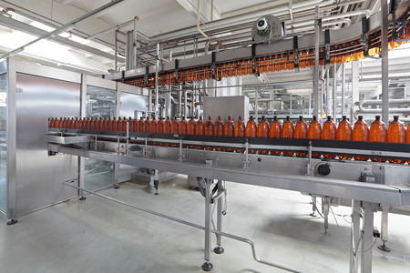 The food industry. Plastic beer bottles moving on conveyor