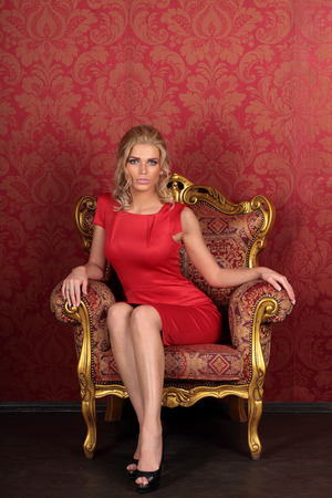 blondie: Beautiful girl in red dress sitting in an antique chair in the room interior