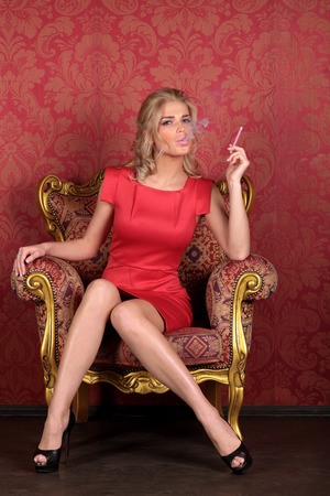 antique chair: Beautiful girl in red dress sitting in an antique chair and smokes in the room interior