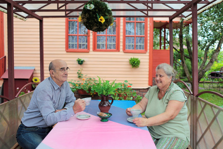 dacha: An elderly married couple drink tea at gazebo about country house