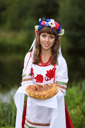 women face stare: Ukrainian girl in national clothes meets guests with handmade bread