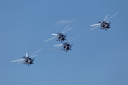 A group of military helicopters flying on the  blue sky