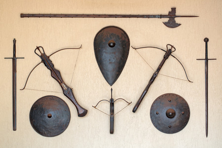 arbalest: The old medieval weapons and shields on the wall Stock Photo