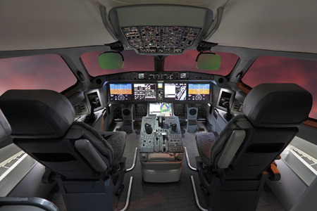 The cabin of the modern passenger airliner, nobody, autopilot, cloudy sunset sky outside the window Editorial