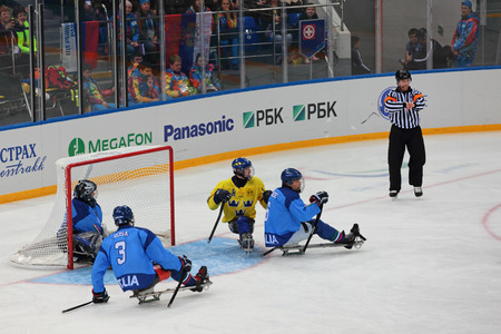 olympiad: SOCHI, RUSSIA - MAR 12, 2014: Paralympic winter games in ice Arena Shayba. The sledge hockey, match Italy-Sweden. The teams in hockey gate