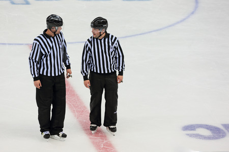 SOCHI, RUSSIA - MAR 12, 2014: Paralympic winter games. Shayba Arena, ice sledge hockey Italy-Sweden. Hockey referees discuss the game