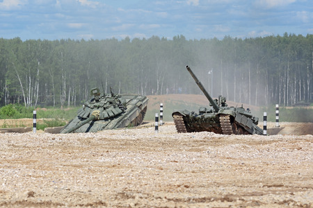 MILITARY GROUND ALABINO, MOSCOW OBLAST, RUSSIA - JUN 18, 2015: Russian tanks in show of military equipment on military ground at the International military-technical forum ARMY-2015. Tanks on the obstacle course