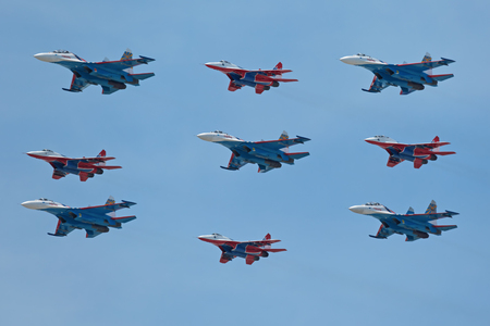 mig: MOSCOW, RUSSIA - MAY 9, 2015: Military parade of 70th anniversaries of a Victory Day in WWII. Flight of aircraft over the city. Aerobatic team Swifts and Russian Knights on the fighters MiG-29 and Su-27