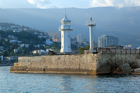 White lighthouse on the pier in the city of Yalta, Republic of Crimea, Russia Stock Photo