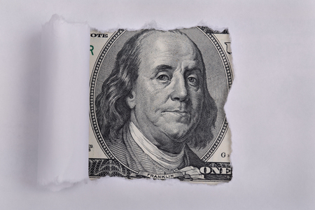 broken through: Portrait of Benjamin Franklin, is depicted on the banknote one hundred dollars USA peeking through broken old sheet of paper Editorial