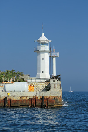 orienting: White lighthouse on the pier in the city of Yalta, Republic of Crimea, Russia Stock Photo