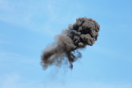 gunfire: Explosion with black smoke against the blue sky