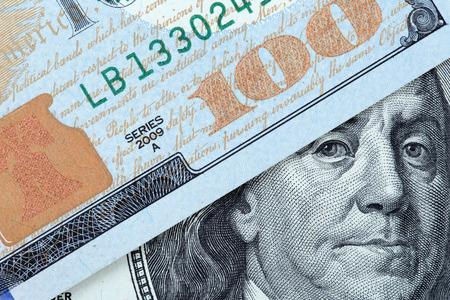 benjamin: Benjamin Franklin peeks out from under the bills of one hundred dollars USA