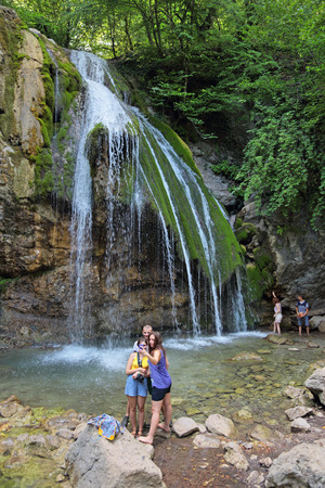 REPUBLIC CRIMEA, RUSSIA - AUG 17, 2014: Tourists photographed against the backdrop of the waterfall Djur-Djur on river Ulu-Uzen East (Megapotamo) on the southern coast of the Crimea in the gorge Khaphal