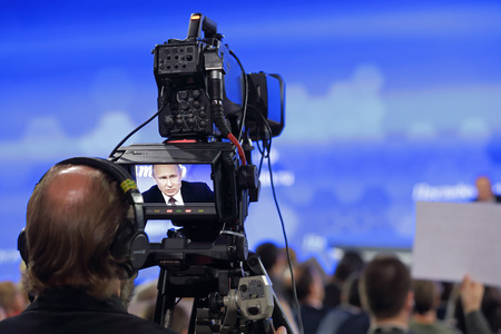live stream tv: MOSCOW, RUSSIA - DEC 23, 2016: Center of international trade. Videographer at the annual press conference of the President of Russia, will broadcast the answers to the questions of Vladimir Putin Editorial