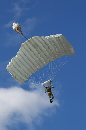 paratrooper: The landing - paratrooper fly in the background of the blue sky Stock Photo