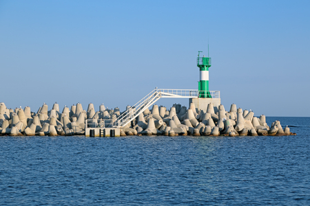 Concrete coastal fortifications (the tetrapods) and modern lighthouse in the commercial port of Sochi, Russia Stock Photo