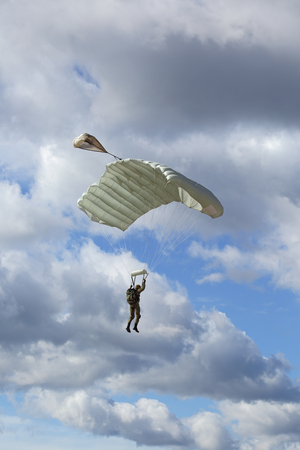 The landing - paratrooper fly in the background of the blue sky Stock Photo