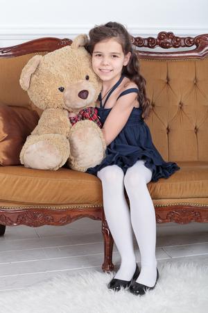 소녀는 소파에 앉아 봉 제 곰 포옹