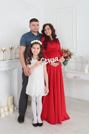 family  room: The young family - father, pregnant mother and daughter, family portrait in the room Stock Photo