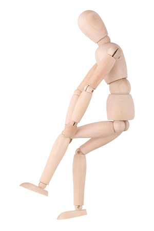 Wooden ball-jointed doll isolated on white background shows pain in the knee joint
