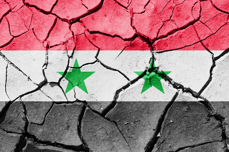 The image of the flag of Syrian Arab Republic on the cracked dry ground