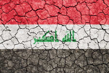 The image of the flag of Iraq on the cracked dry ground Фото со стока
