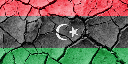 The image of the flag of Libya on the cracked dry ground