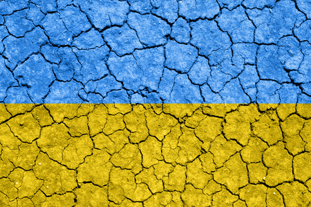 The image of the flag of Ukraine on the cracked dry ground