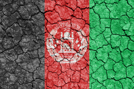 The image of the flag of Islamic Republic of Afghanistan on the cracked dry ground