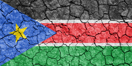 The image of the flag of Republic of South Sudan on the cracked dry ground Stock Photo