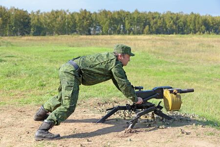 Soldier in camouflage uniforms fires automatic grenade launcher Imagens