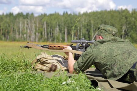 A soldier in camouflage uniform shoots a sniper rifle sitting