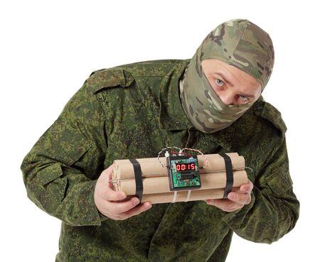 Saboteador en camuflaje y un casco Balaclava con explosivos en las manos, aislado sobre fondo blanco.