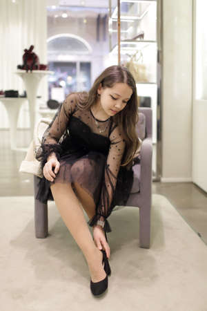 A teenage girl in a black dress tries on shoes in a store