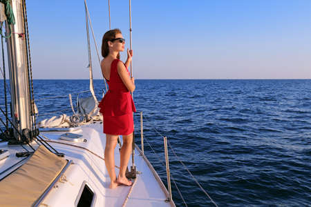 A young girl stands on a yacht and looks into the distance