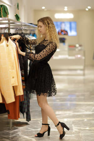 A teenage girl in a black dress chooses clothes in a store