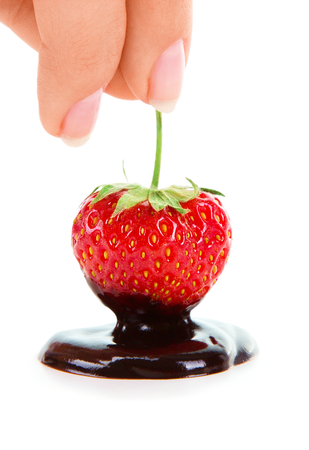 Woman hand holding chocolate-dipped strawberry on the white background photo