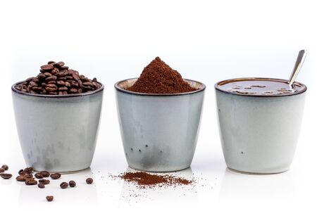 3 rustic coffee cups filled with hot coffee, beans, and ground coffee. Cups standing on a slightly reflective table that fades into a white background