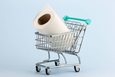 Toilet paper roll in a miniature shopping cart on a blue background.Concept of hoarding and panic buying toilet paper during the Covid-19 pandemic.
