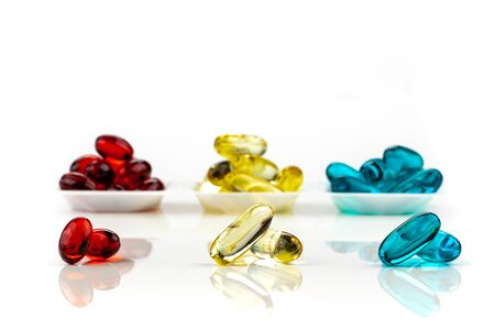 A mix of multicolored medical soft gel capsules on a white background - medical supplements , red, yellow, blue