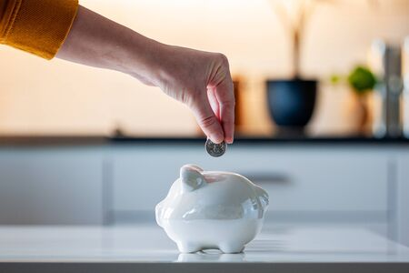 Personal finances, woman putting money into a piggy bank- -wealth and financial concept. White piggy bank in the foreground. Фото со стока