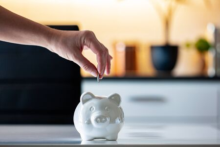 Personal finances, woman putting money into a piggy bank- -wealth and financial concept. White piggy bank in the foreground. Stok Fotoğraf