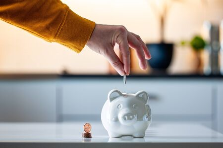 Personal finances, woman putting money into a piggy bank- -wealth and financial concept. White piggy bank in the foreground. 写真素材
