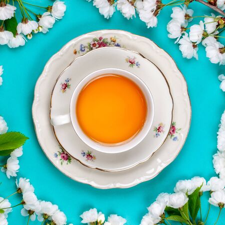 Traditional tea cup and saucer on a pastel blue background. Golden tea with honey. Flat lay, top view.
