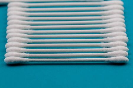 Q-tips, cotton swabs, isolated on bright blue background.
