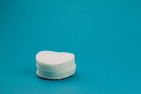 Q-tips, cotton swabs, cotton pads, isolated on bright blue background. Banque d'images