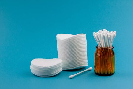 Q-tips, cotton swabs, cotton pads, isolated on bright blue background. Amber bottle 写真素材