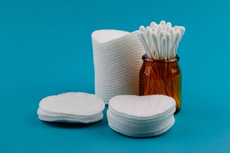 Q-tips, cotton swabs, cotton pads, isolated on bright blue background. Amber bottle Stok Fotoğraf