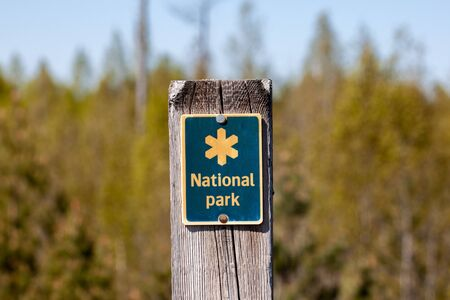 A pole with a yellow and blue National park sign. Forest in the background - Sweden